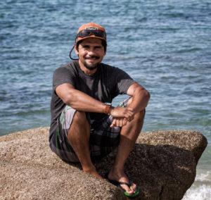 Roger Herrera sitting on a rock near the ocean.