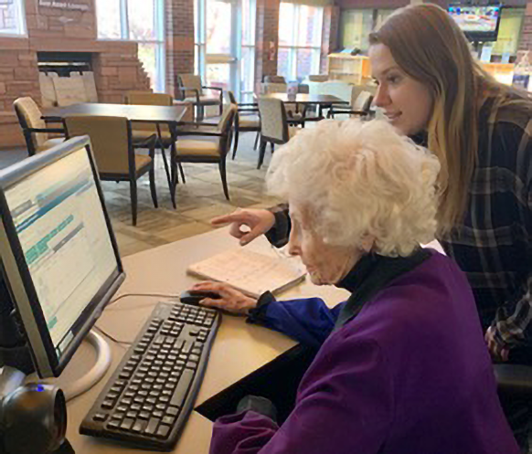 Young person helping older woman with computer