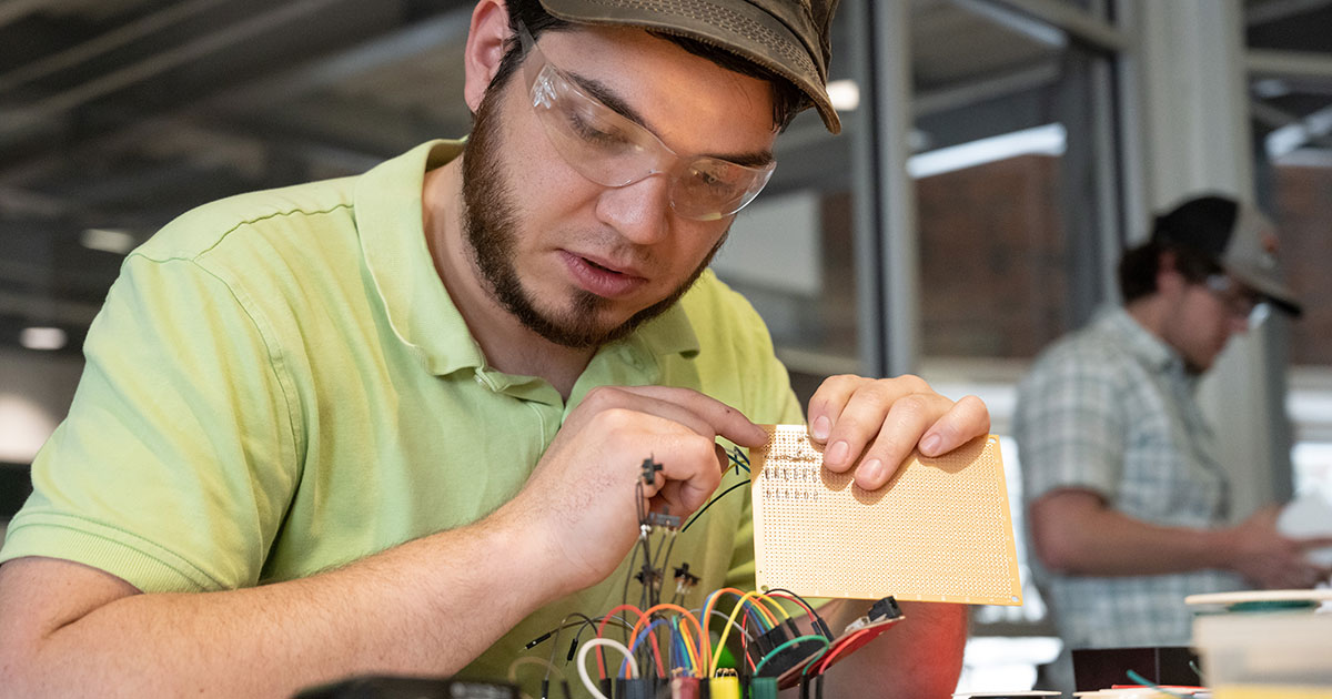 student with circuit board in rapid prototyping lab