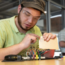 Student with circuitry board in rapid prototyping lab