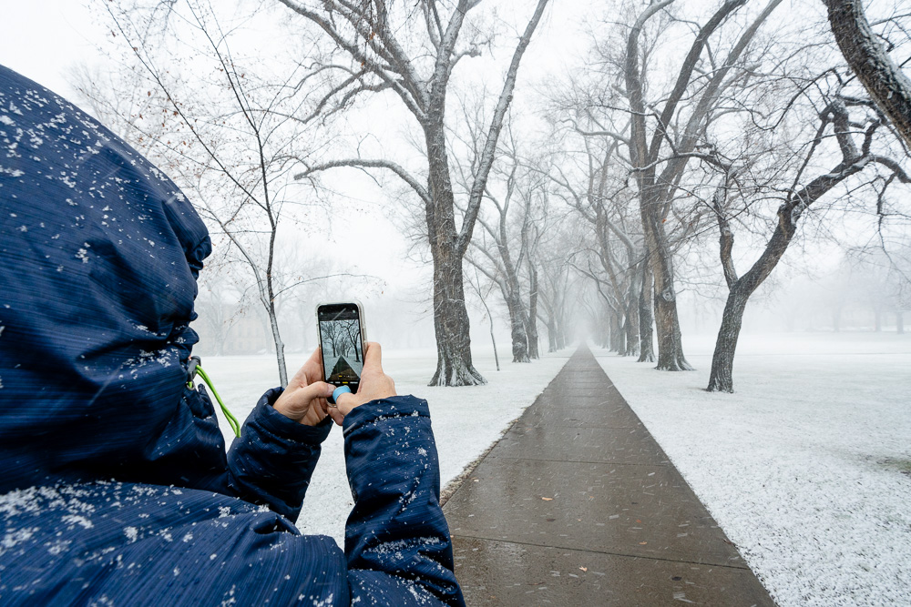 Person in parka photographing empty Oval