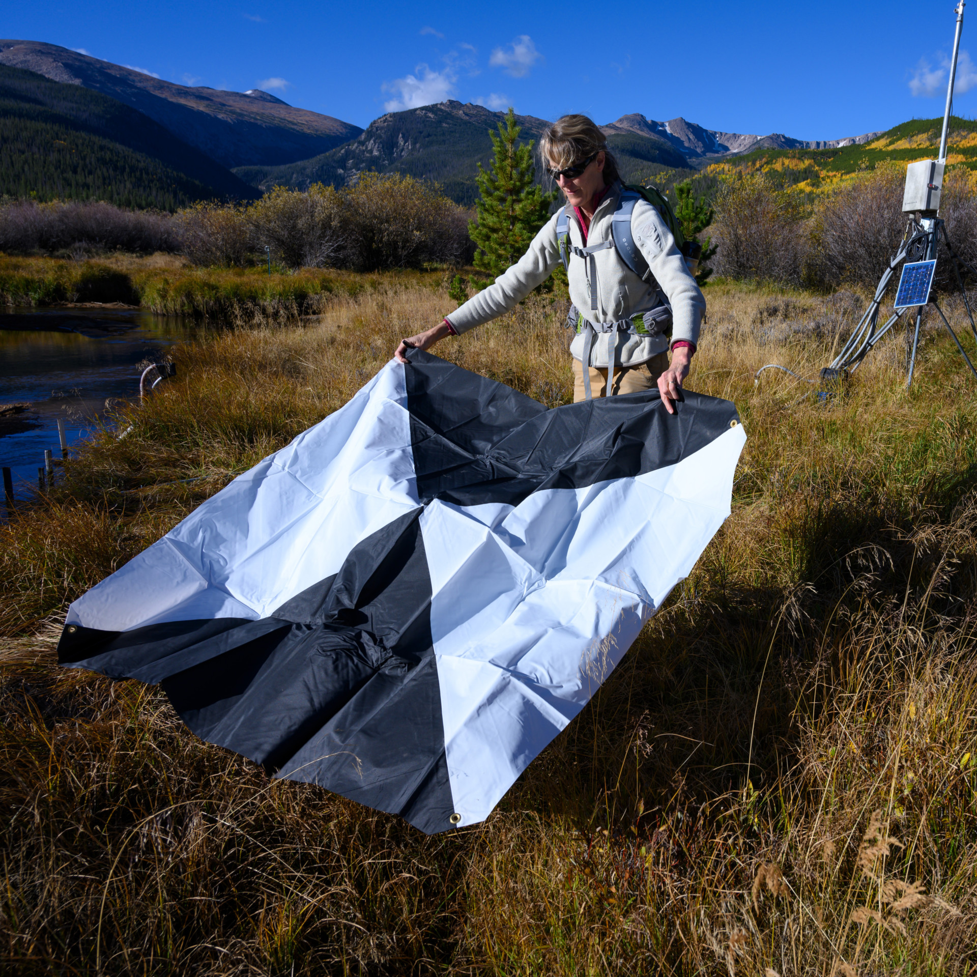 Colorado State University Geosciences professor Sara Rathburn sets up ground reference targets in preparation for an aerial survey of Pingree Park using drone imagery at CSU's Mountain Campus
