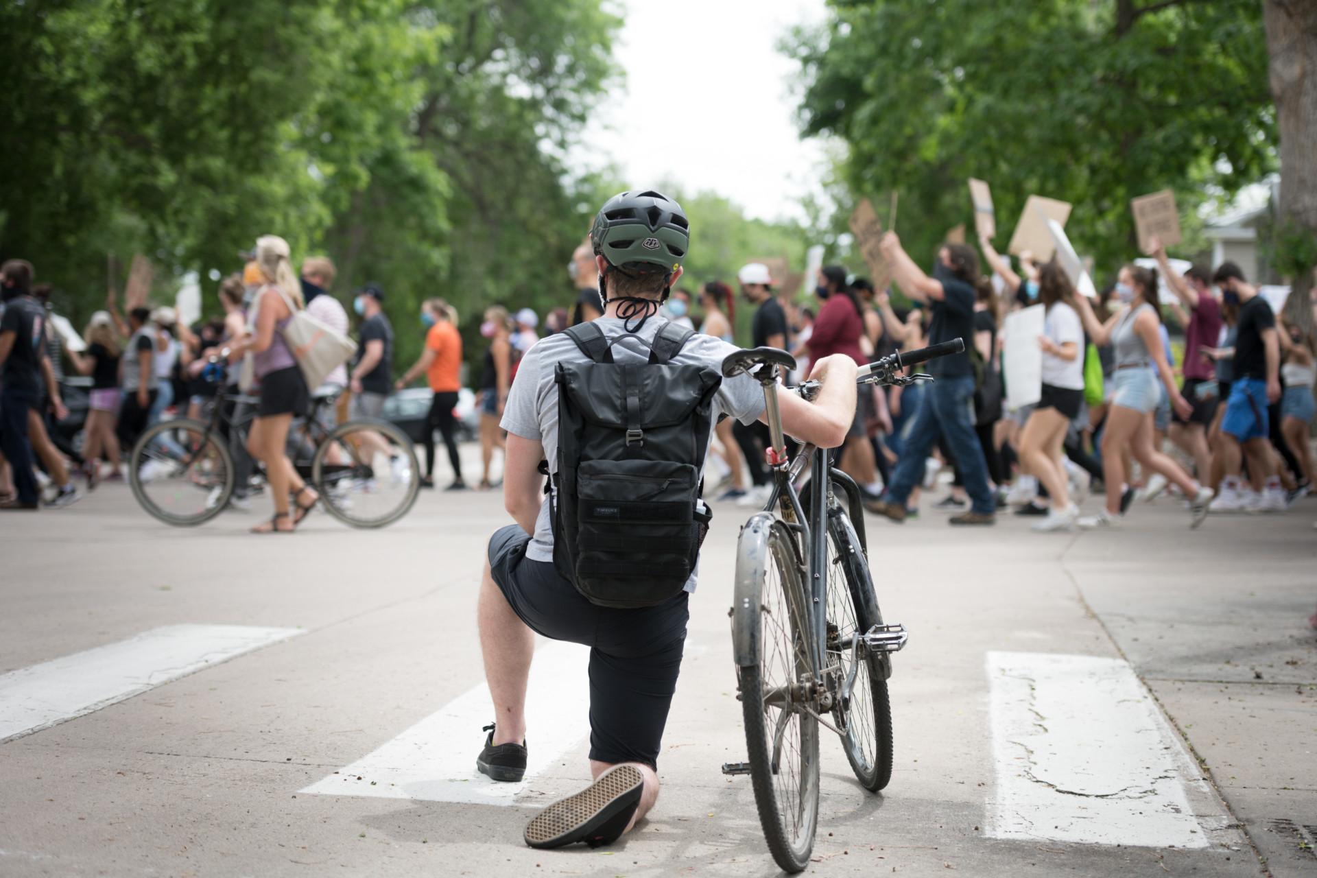 Bicyclist kneeling as march crosses street