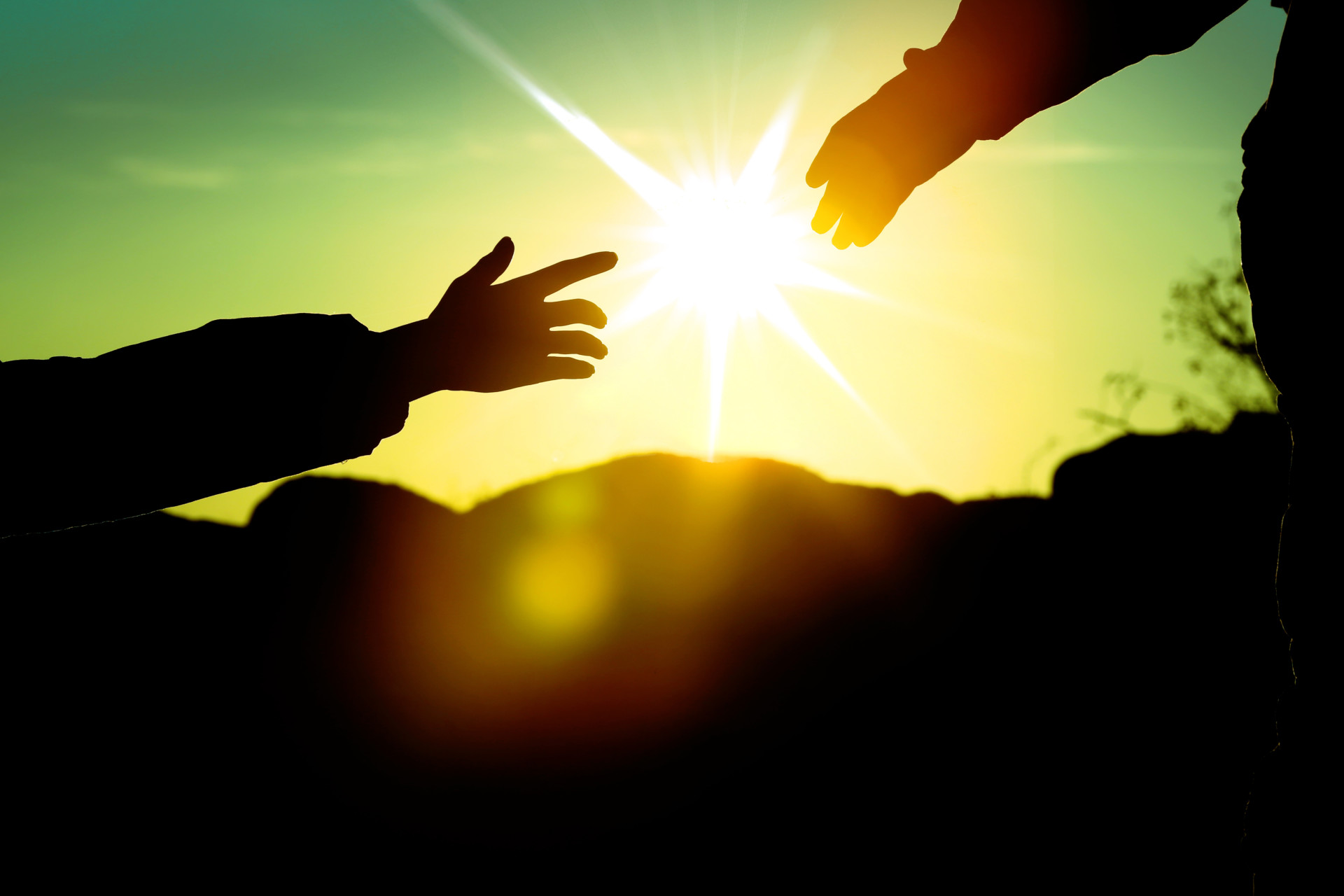 Hands reaching to each other with sunset between