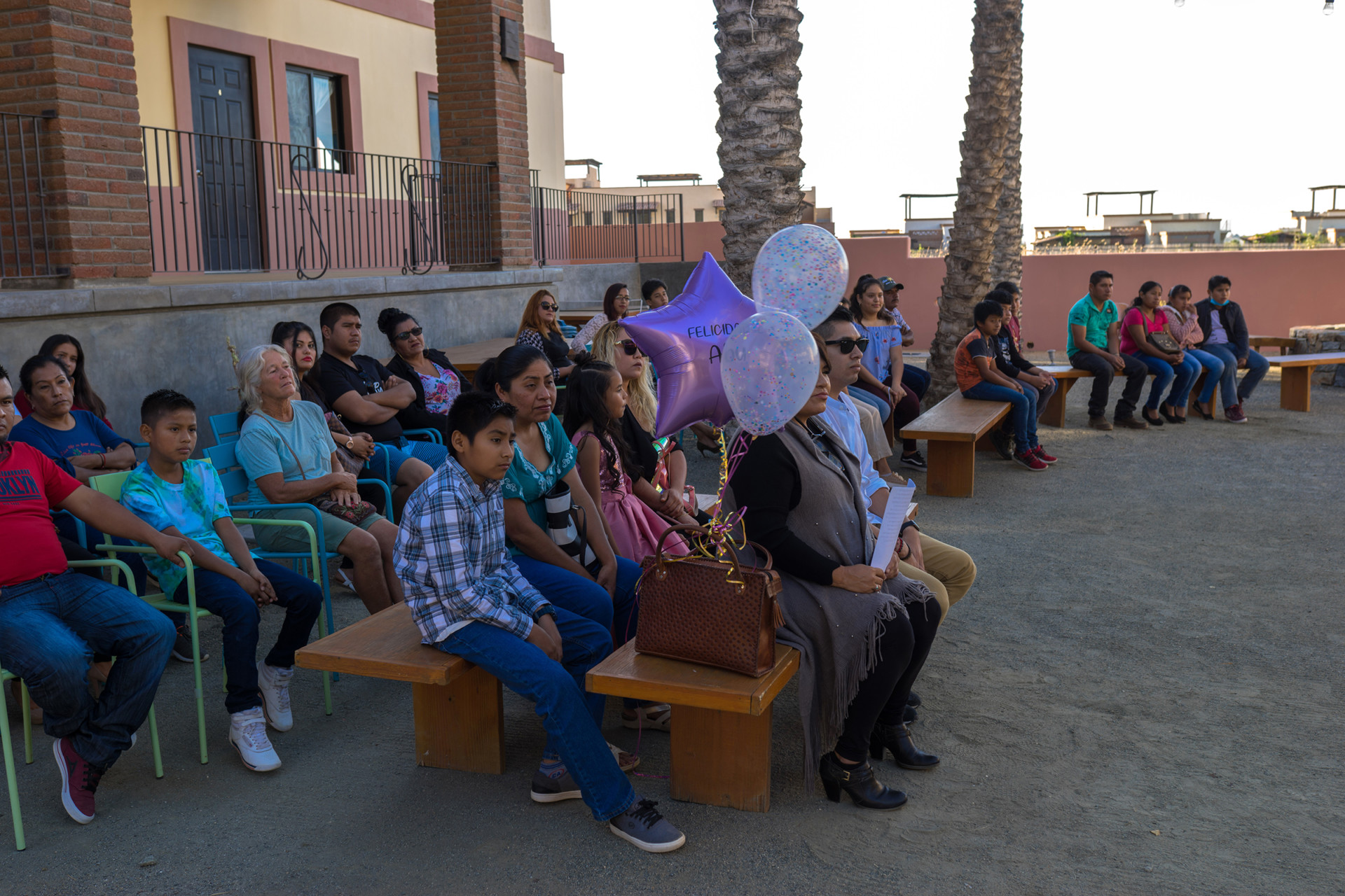 A group sits on a bench with balloons.