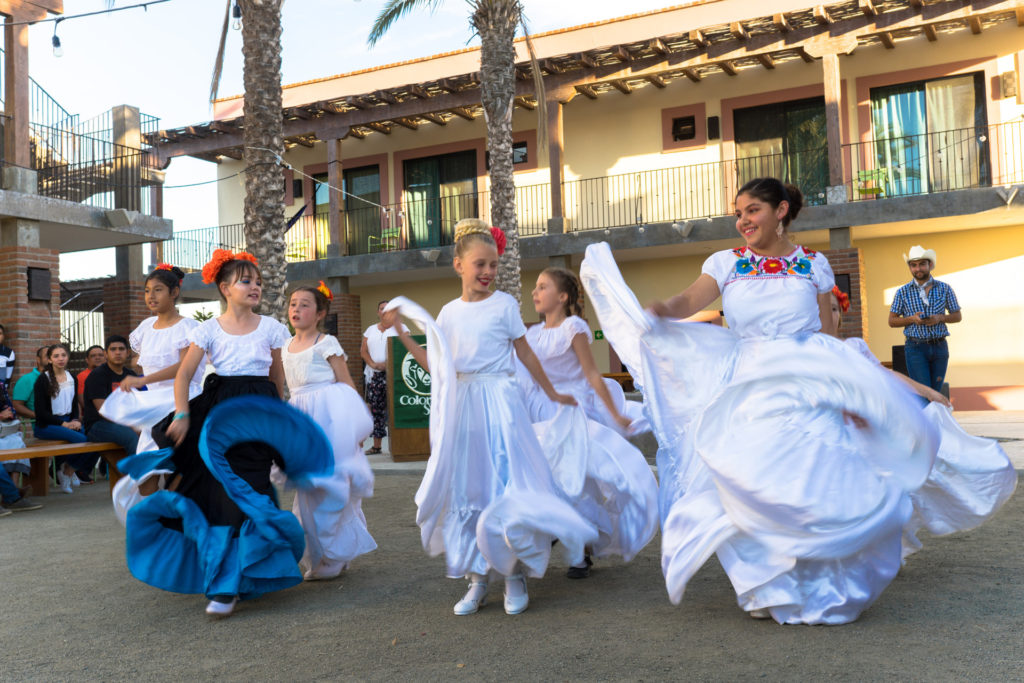 Children in white dresses dancing.