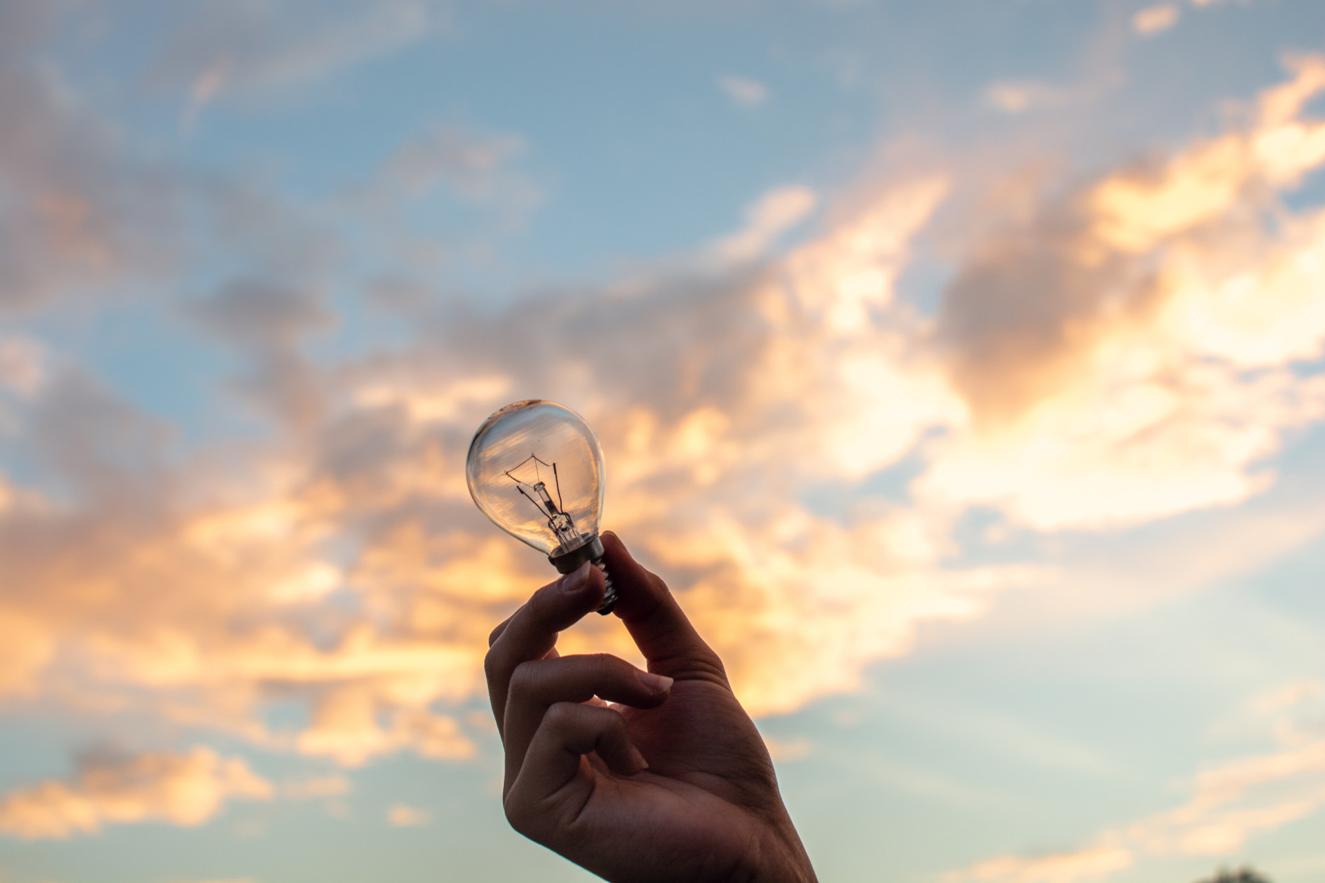 a hand holding a clear light bulb with sunset in the background