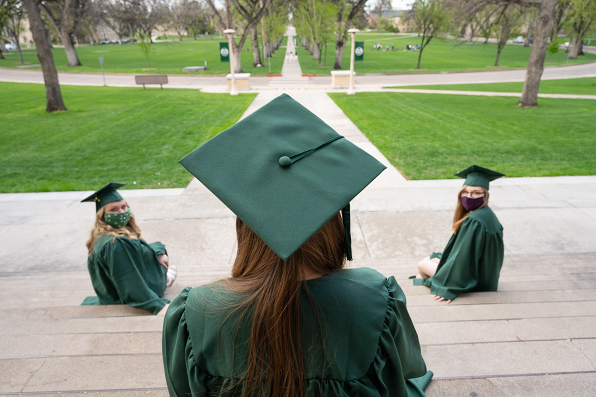 Photo of three students graduating on the Oval