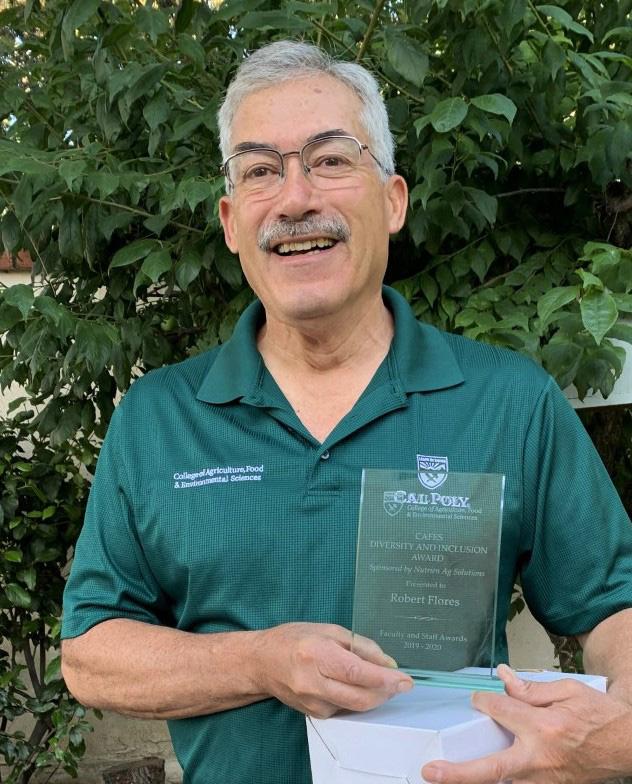 Robert Flores holding a diversity award