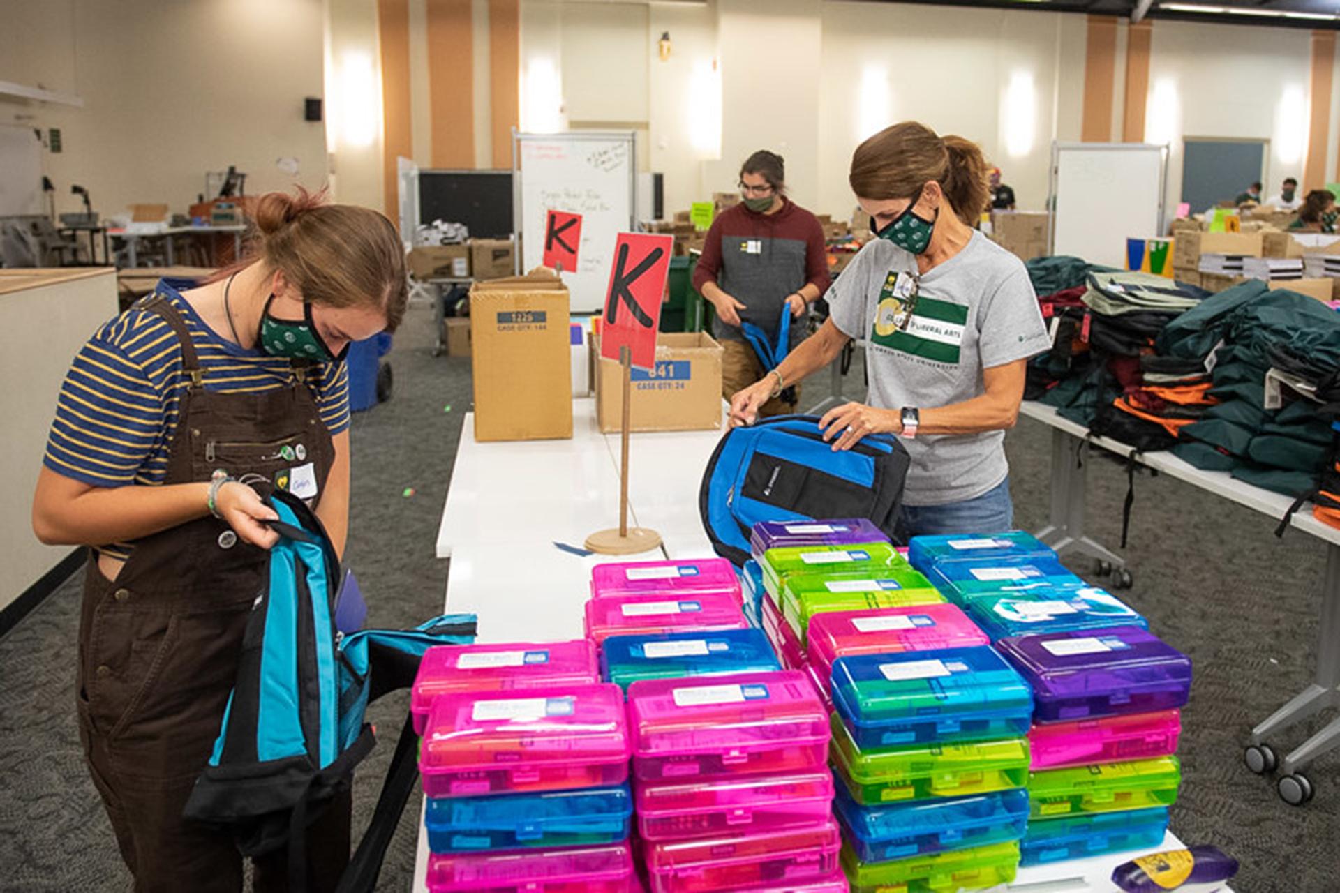 School Is Cool volunteers packing backpacks