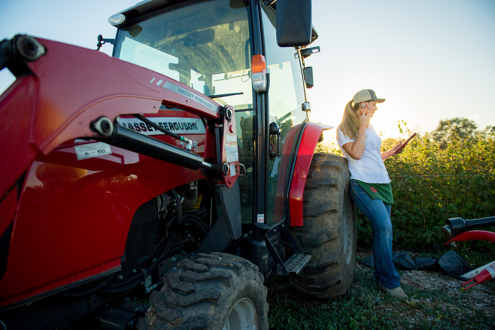 Woman on cellphone with tractor