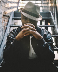 CSU alum Ebenezer Yebuah sitting on outdoor staircase with a black shirt and fedora.