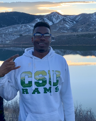 CSU student Jamar Cook stands in front of Horsetooth Reservoir during sunset, wearing white CSU Rams hoodie and glasses.