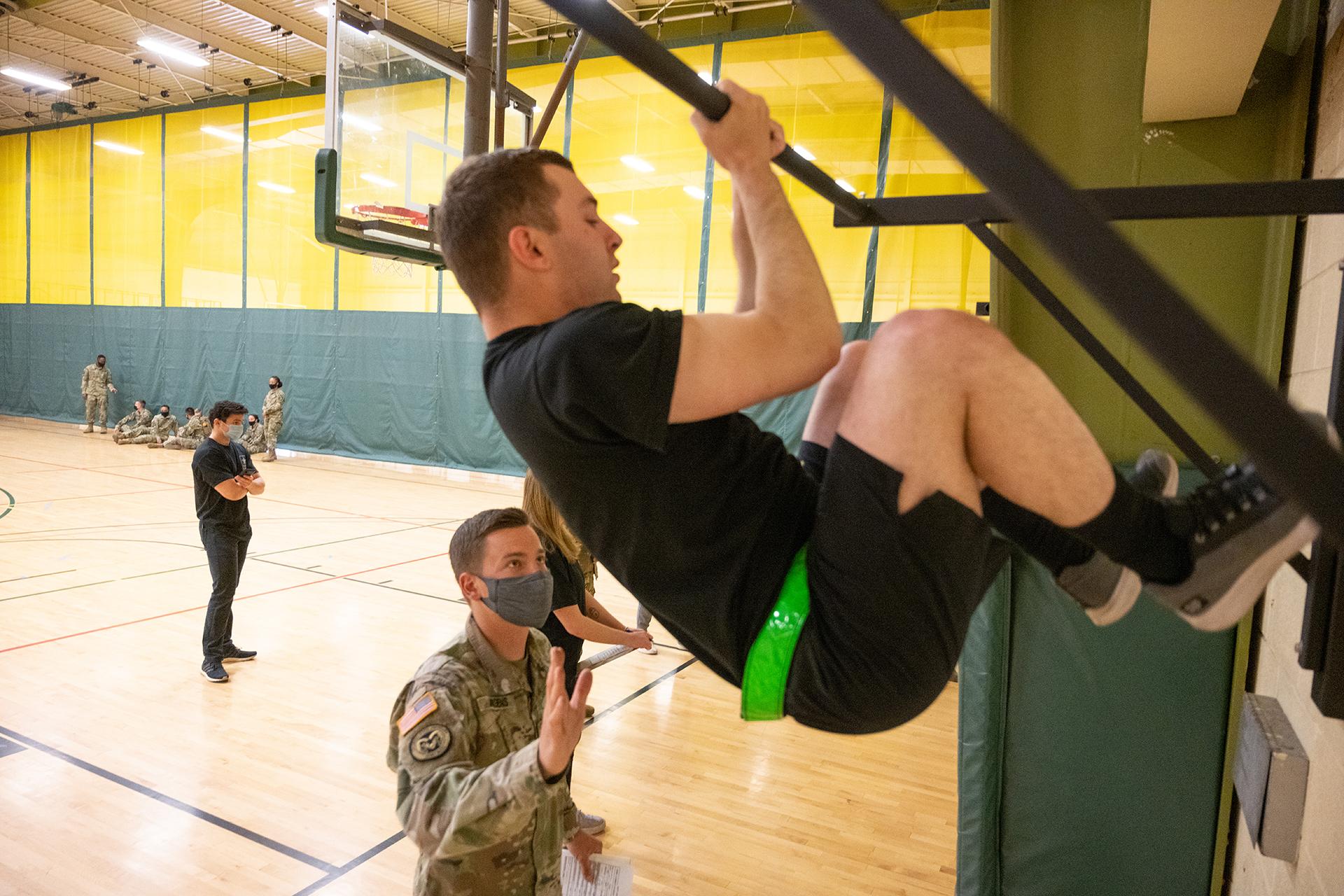 CSU Army ROTC cadet doing leg tucks in gym