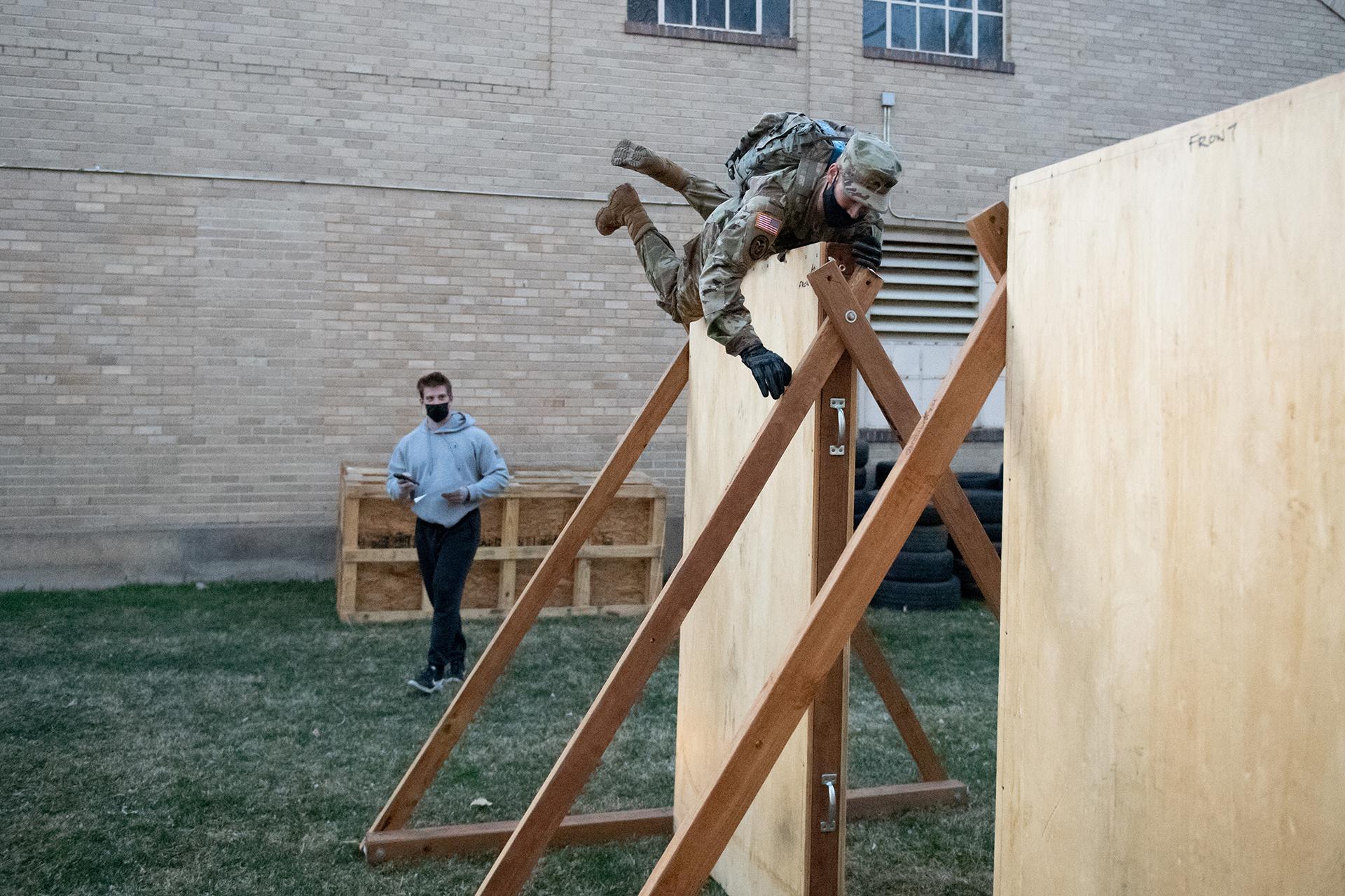 CSU Army ROTC cadet climbing over a wall