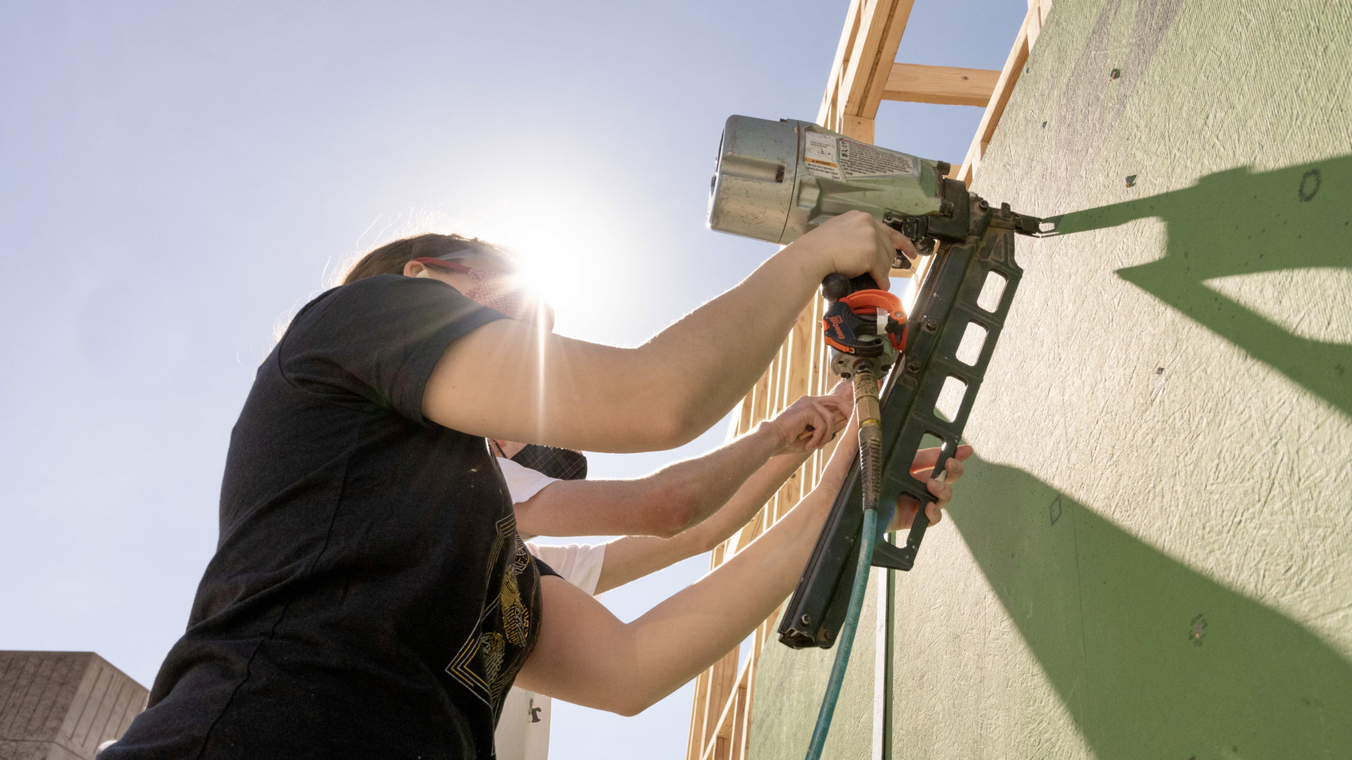 Student uses nail gun during construction of tiny house on wheels at the Nancy Richardson Design Center.