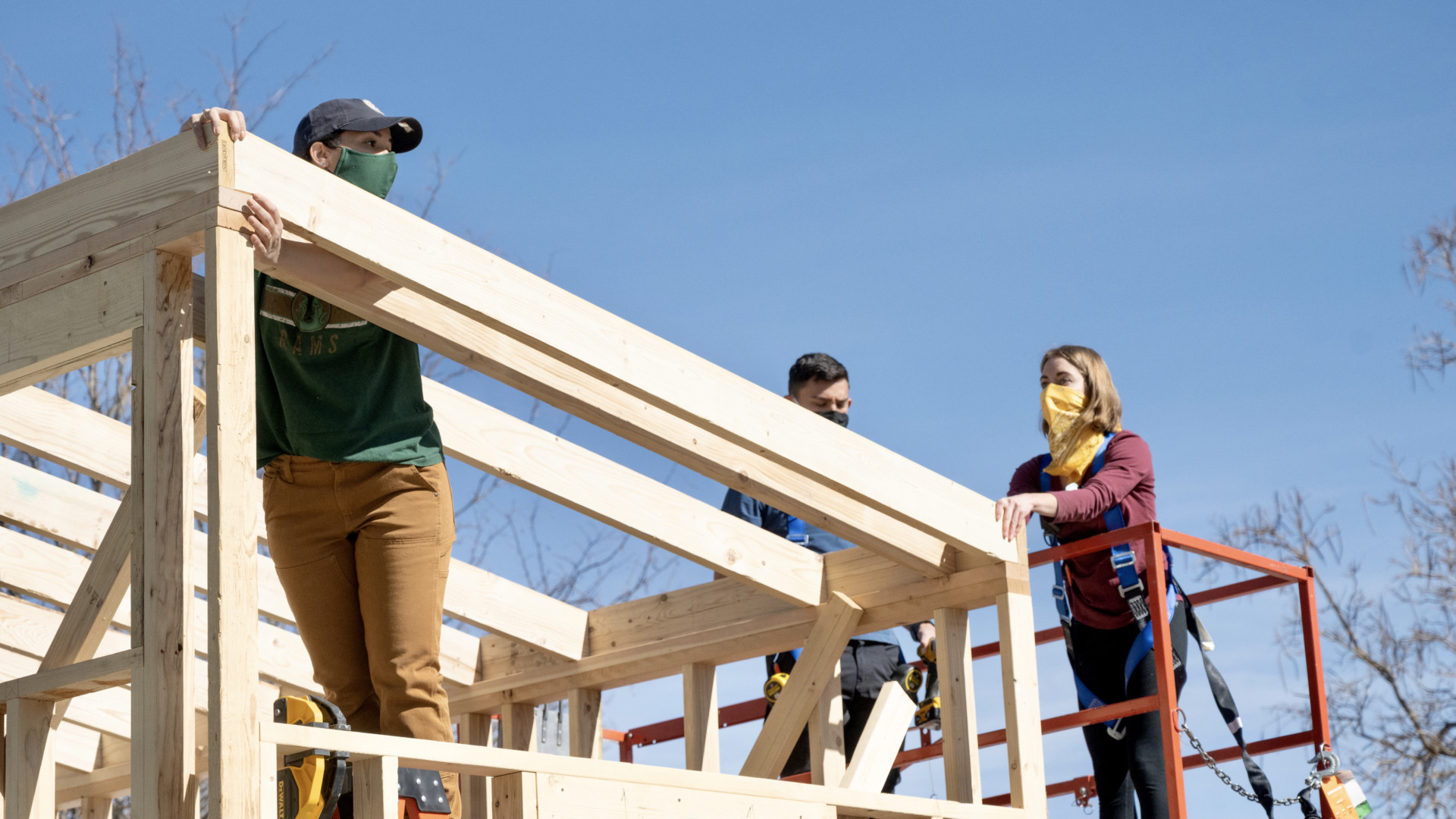 Students stand on scaffolding and wooden frame of tiny house on wheels, during construction on sunny day at the Nancy Richardson Design Center, March 6, 2021.