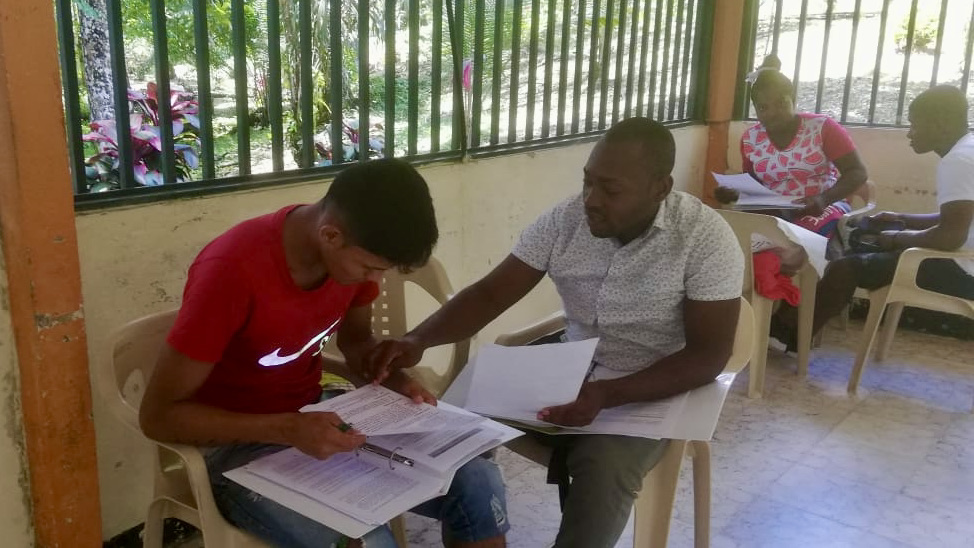 Two student trainees practicing interviewing. Student on the left, wearing a red shirt, looks at an open book as the student on the right, wearing a white polo, points to the papers and open book on a desk in front of the other student.