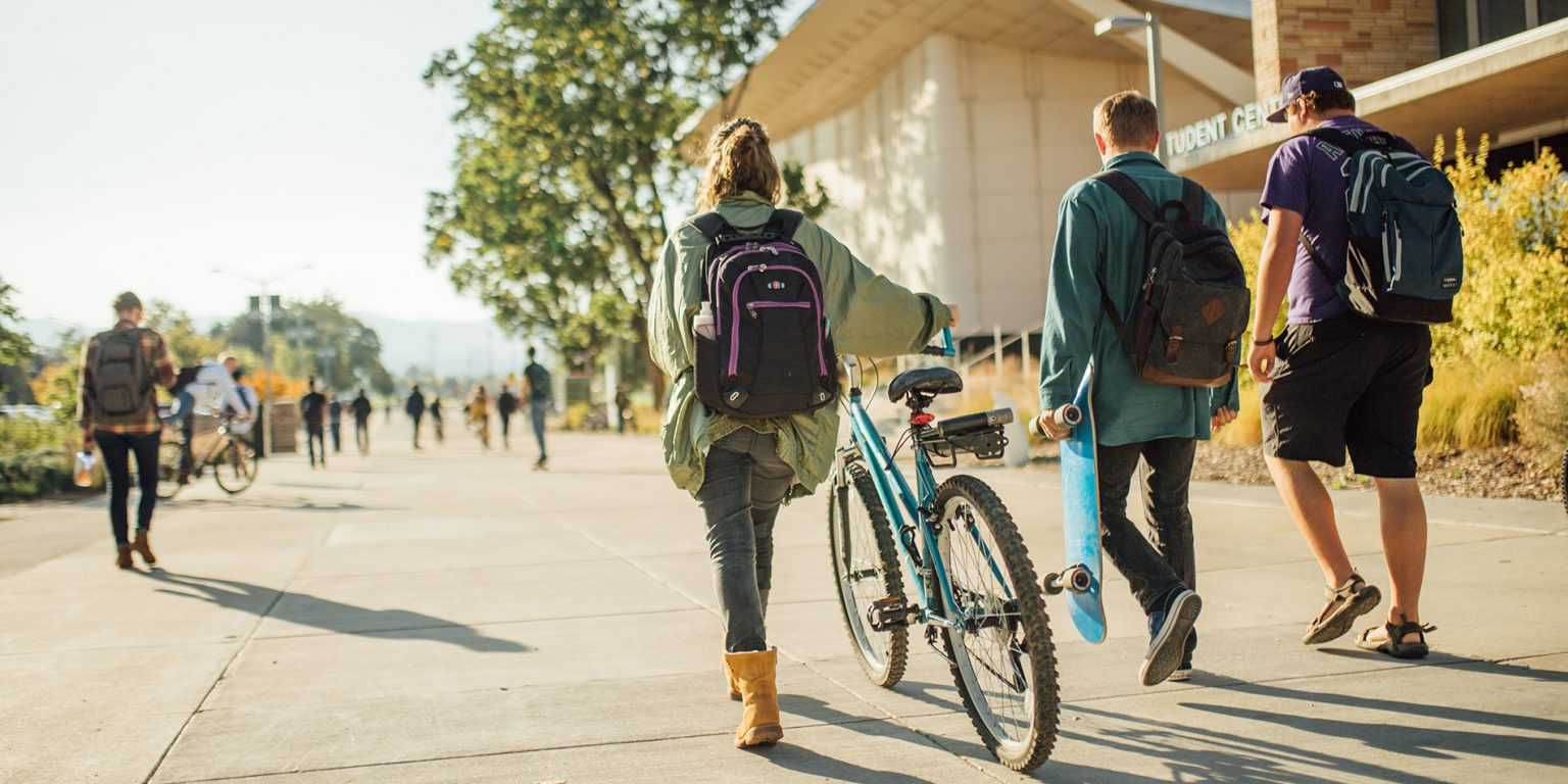 Students walking bike on campus