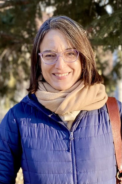 Marcela Velasco smiling, outside on sunny day with blurred backdrop of trees, wearing prescription glasses, a scarf, and a blue puffy jacket.