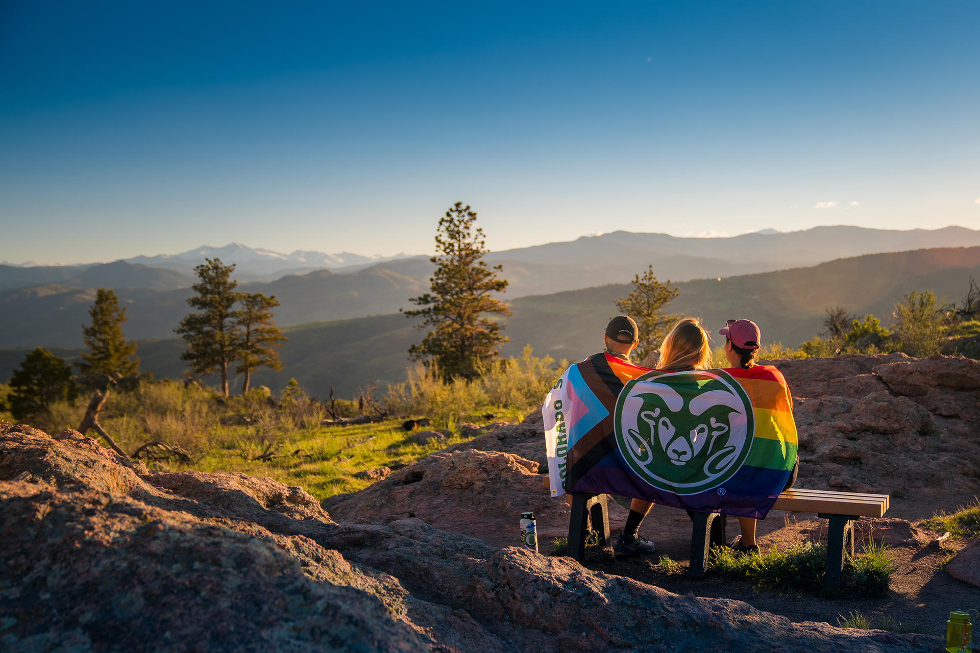 CSU students with Pride Flag sitting on bench