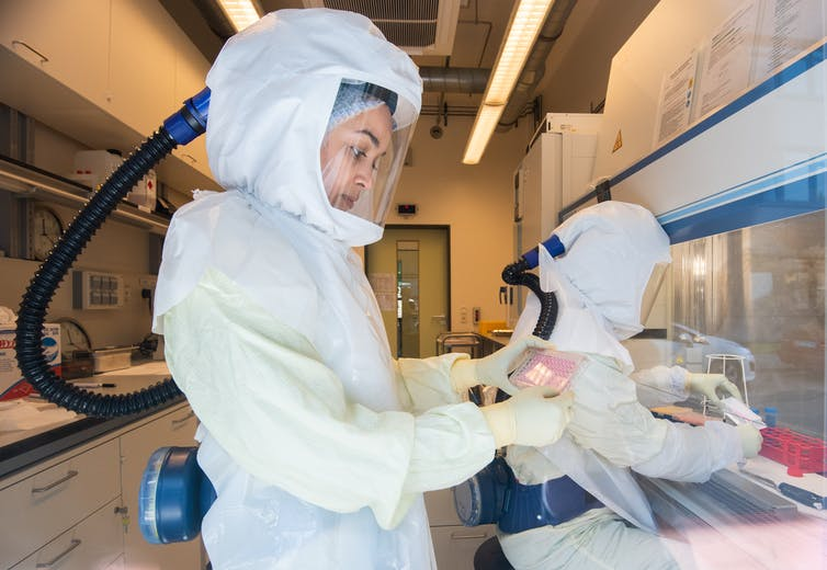 Researchers in containment suits