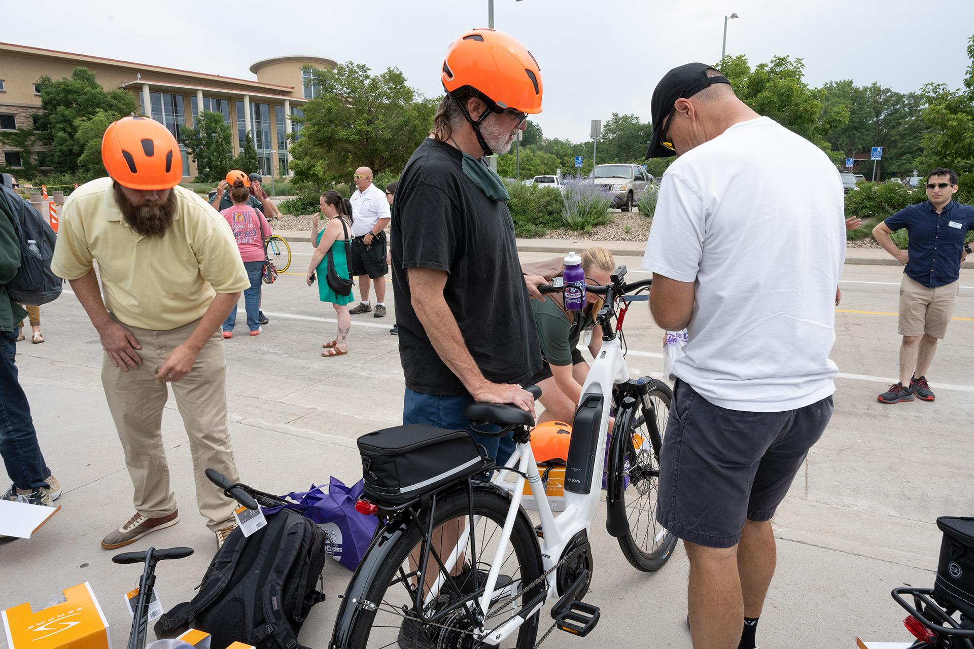 CSU employee with orange helmet prepares to ride e-bike
