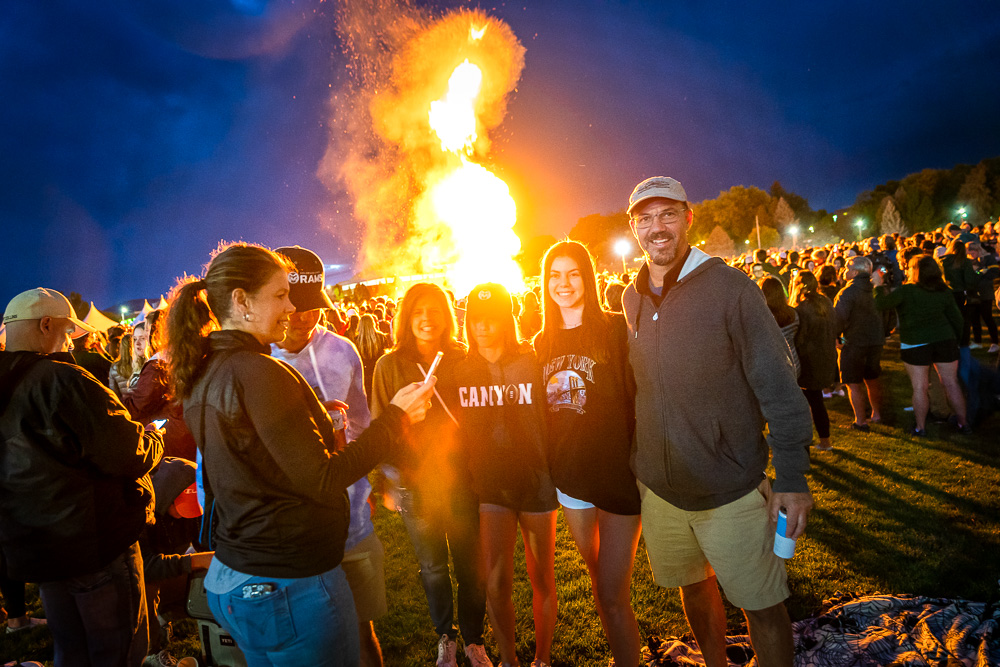 A family gathers at the homecoming bonfire
