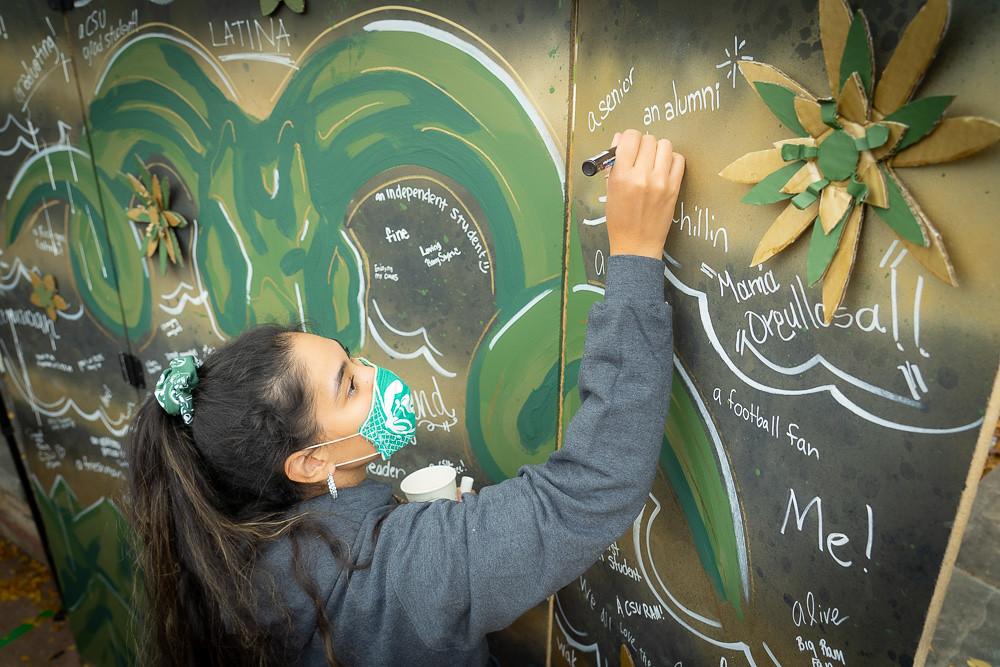 Student signs board at homecoming